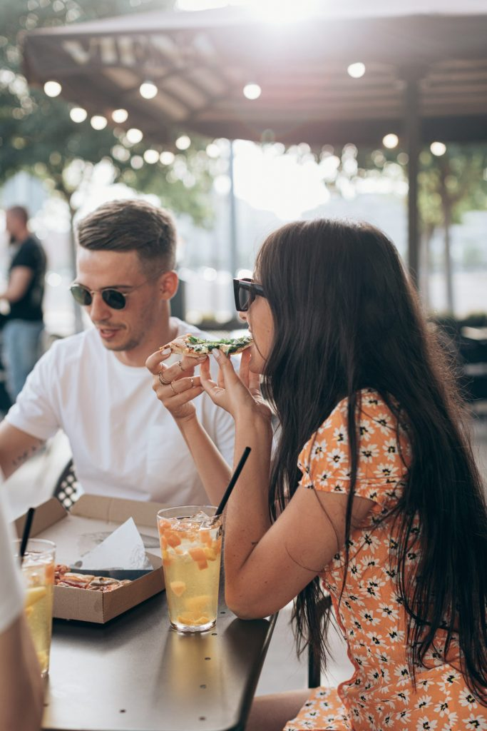 Couple eating a pizza in a bar.